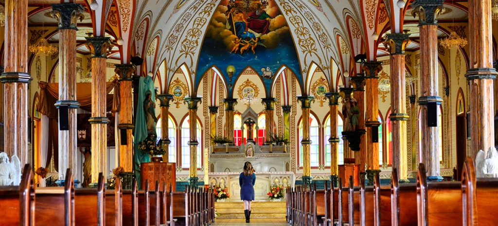 Young girl in front of beautiful church viewing the renovated alter made possible with church financing