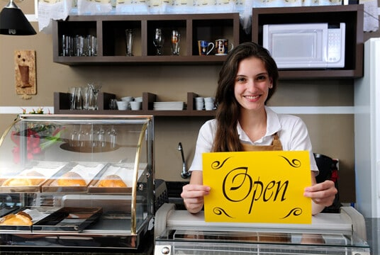 Store owner holding open sign thanks to small business grants