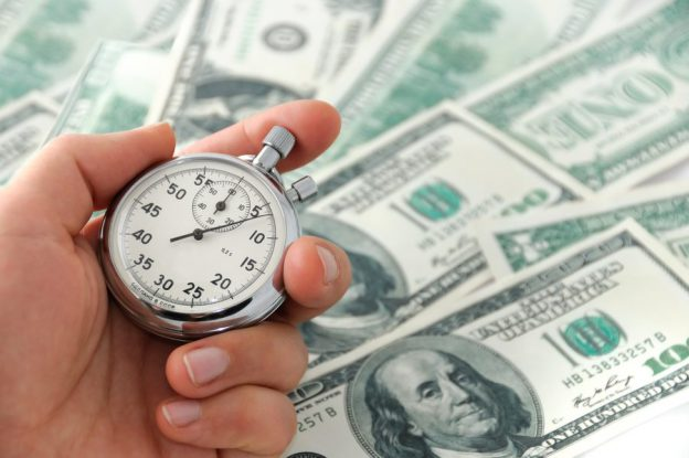 Stop watch with cash showing fast business funding