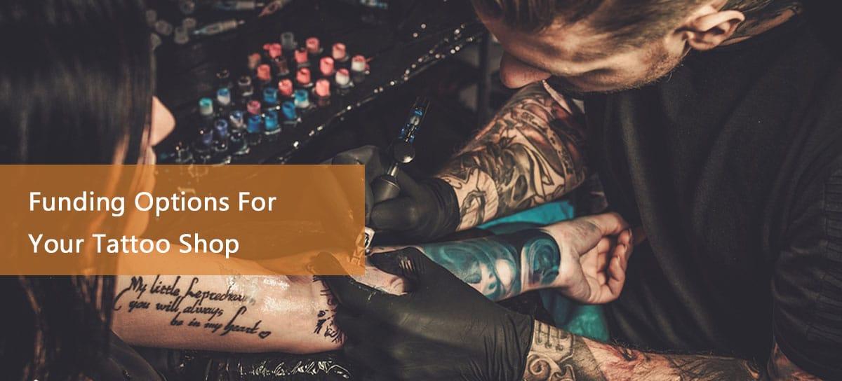 Tattoo artist inking customer thanks to a tattoo shop loan