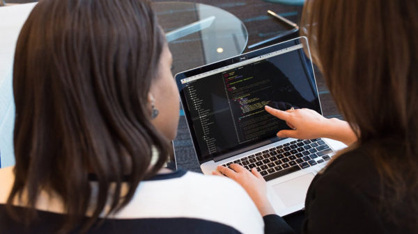 Two women looking at laptop establishing their startup's visual brand identity