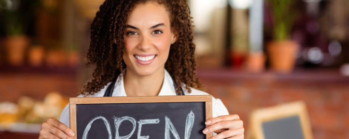African American female business owner holding an open sign