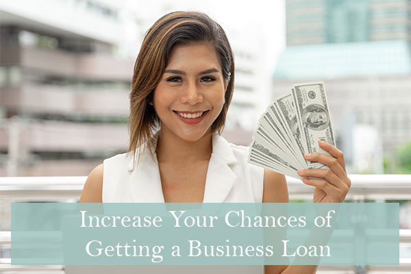Woman holding up cash after improving her chance of getting a business loan
